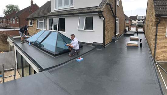 GRP fibreglass roof Hertfordshire contractors. Herkomer roofers on top of customers roof finishing the roofing work.