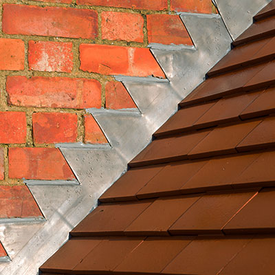 Closeup of new plain red clay tiles and lead flashing on a pitched roof in the UK.